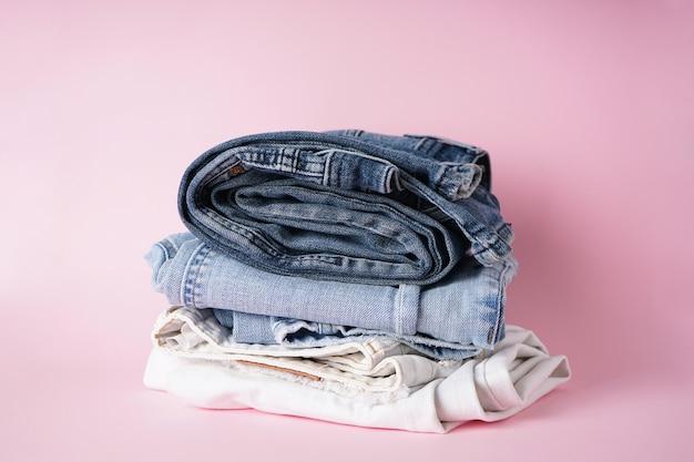 Składane różne dżinsy na różowym tle.