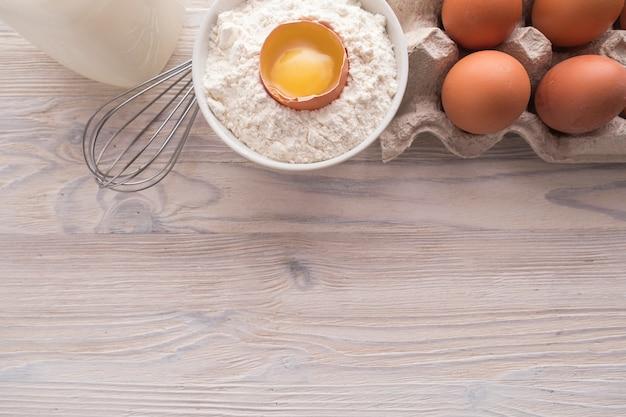 Składanie na płasko składników do pieczenia. mąka, jajka, mleko, żółtko na stole. koncepcja pieczenia słodkiego ciasta. widok z góry