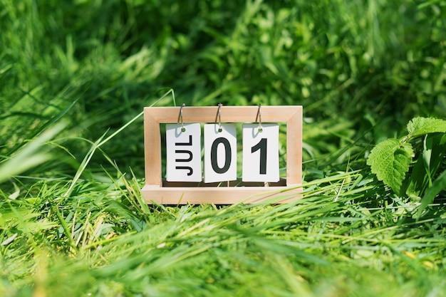 Składany kalendarz z datą 1 lipca na trawiastym trawniku.