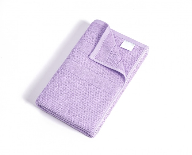 Składany miękki fiołkowy ręcznik frotte z białą pustą etykietą na białym tle