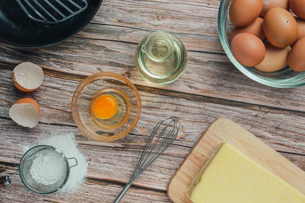 Składnik do pieczenia: mąka, jajko, mleko i wałek do ciasta, widok z góry