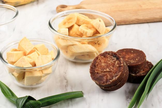 Składnik preparat do przygotowania kompotu z bananów i słodkich ziemniaków (kolak pisang ubi). krojenie banana, słodki ziemniak w plasterkach, cukier palmowy (gula merah), liście pandan. popularny na ramadan