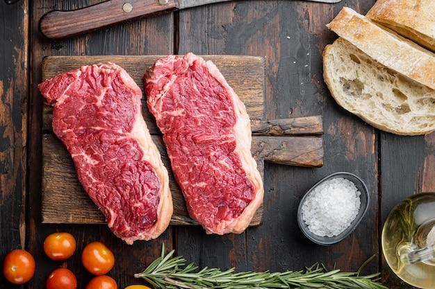 Składniki burgera stek z wołowiną, mięsem marmurkowym, na ciemnym drewnianym stole, widok z góry