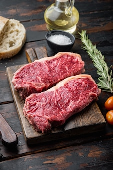 Składniki burgera stekowego z wołowiną, mięsem marmurkowym, na ciemnym drewnianym stole,