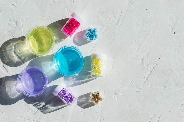 Składniki, butelki, słoiki do wyrobu, ozdabianie popularnej zabawki dziecięcej z kleju. domowy niebieski, fioletowy, żółty modny szlam z kulkami dla rozrywki i hobby w okrągłych pudełkach.