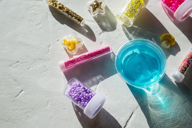 Składniki, butelki, słoiki do wyrobu, ozdabianie popularnej zabawki dziecięcej z kleju. domowy niebieski modny szlam z kulkami dla rozrywki i hobby w okrągłych pudełkach.