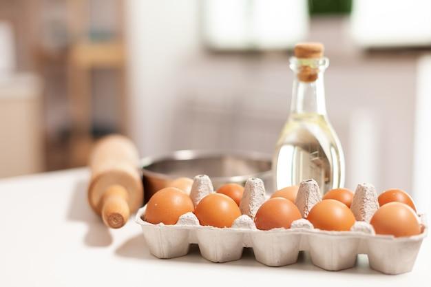 Składniki ciasta na domowe ciasta i chleb w pustej kuchni. nowoczesna jadalnia wyposażona w naczynia gotowe do gotowania z mąką pszenną w szklanej misce i świeżymi jajkami na stole