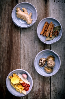 Składniki dla chińskiej ziołowej zupy na podławym drewnianym tle.