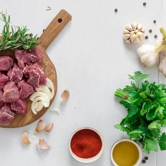 Składniki dla gotować mięso z warzywami na białego drewnianego tła odgórnym widoku. przygotowanie mea wołowego