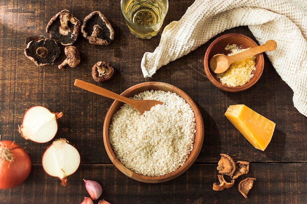 Składniki dla robić risotto grzybowi na nieociosanym drewnianym stole