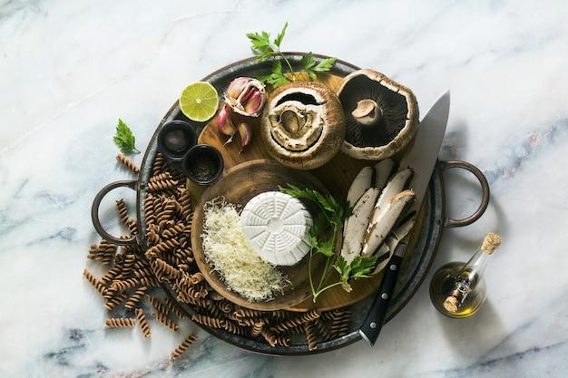 Składniki do bezglutenowego gotowania makaronu fusilli z pół-ziarna mąki farro z grzybami portobello i serem ricotta na tacy na marmurowym stole. gotować zdrowe przepisy