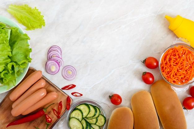 Składniki do gotowania hot-dogów na kuchennym stole. widok z góry, płaski układ. fast food. uliczne jedzenie.