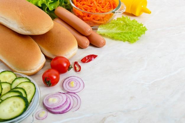 Składniki do gotowania hot-dogów na kuchennym stole. zamknij się, skopiuj miejsce. fast food. uliczne jedzenie.