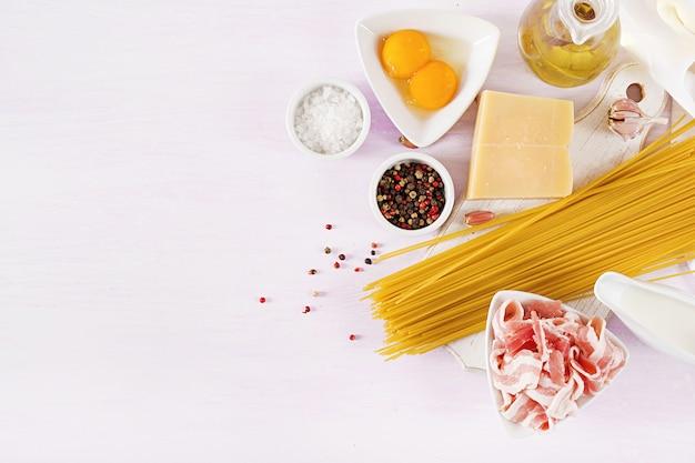 Składniki do gotowania makaronu carbonara, spaghetti z pancettą, jajko, papryka, sól i twardy parmezan.