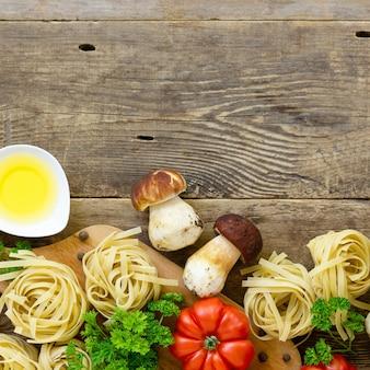 Składniki do gotowania makaronu. fettuccine z borowikami, pomidorem i zielenią na starym drewnianym tle.