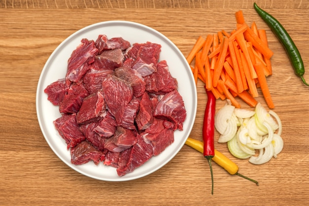 Składniki do gotowania pilaw na drewnianym tle. cebula, papryka, marchewka, mięso mielone leżą na drewnianej desce do krojenia. gotowanie pilaw w domu.