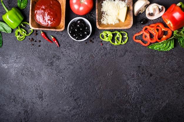 Składniki do gotowania pizzy. sos pomidorowy, papryka słodka, oliwki, ser, pieczarki i bazylia na czarnym tle.