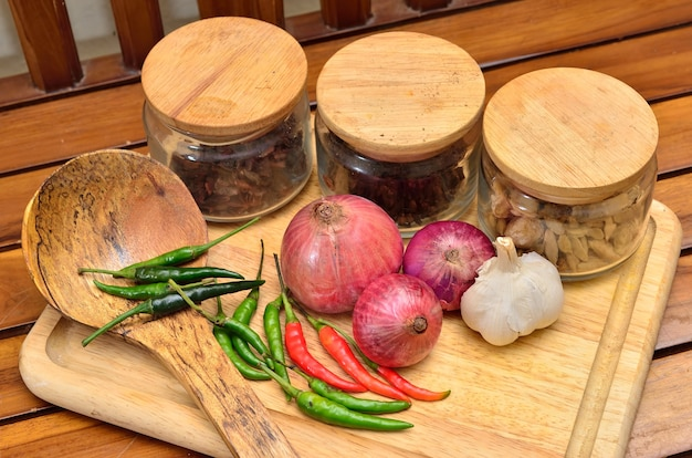 Składniki do gotowania. przyprawa i zioła z cebulą i czosnkiem na drewnianej desce