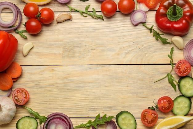 Składniki do gotowania sałatki. rama różnych warzyw i przypraw marchew, pomidor, cebula, ogórek, papryka i rukola na naturalnym drewnianym stole. widok z góry.