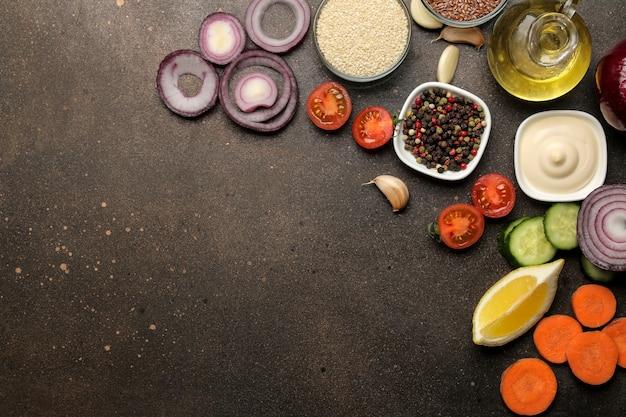 Składniki do gotowania sałatki. różne warzywa i przyprawy marchew, pomidory, cebula, ogórki, papryka i rukola na ciemnym tle. widok z góry.