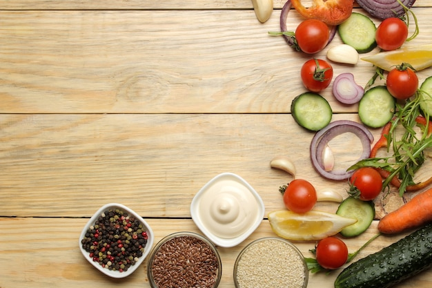 Składniki do gotowania sałatki. różne warzywa i przyprawy marchew, pomidory, cebula, ogórki, papryka i rukola na naturalnym drewnianym stole. widok z góry.