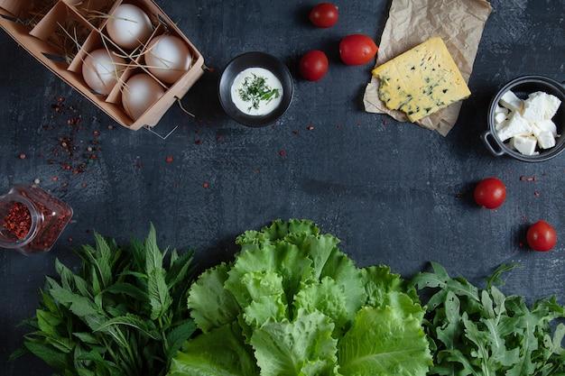 Składniki do gotowania sałatki. świeże, ekologiczne warzywa, ekologiczne jajka i warzywa. pomidor i sery na ciemny kamienny stół z miejsca kopiowania. leżał płasko. koncepcja zdrowej żywności