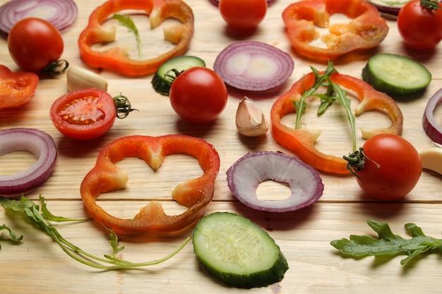 Składniki do gotowania sałatki. tło z różnych warzyw i przypraw marchew, pomidor, cebula, ogórek, papryka i rukola na brązowym drewnianym stole.