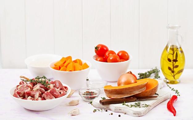 Składniki do gotowania serc kurczaka z dynią i pomidorami w sosie pomidorowym. dekorację podaje się z gotowanym ryżem.