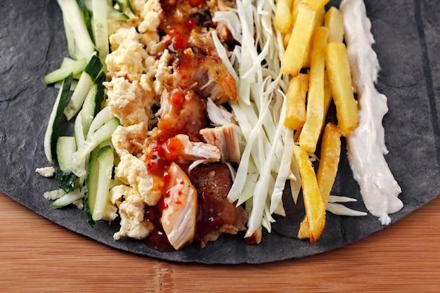Składniki do gotowania shawarmy leżą na chlebie pita. danie z bliskiego wschodu do grillowania.
