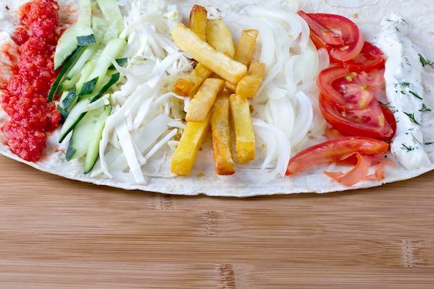 Składniki do gotowania shawarmy leżą na chlebie pita. danie z bliskiego wschodu na grilla.