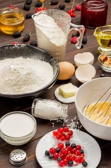 Składniki do gotowania śniadania. mąka jagodowa, trzepaczka do jajek, konfitura miodowa, jogurt na stole. widok z góry.