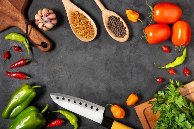 Składniki do gotowania z pomidorami, różnymi paprykami, czosnkiem i zieloną papryką.