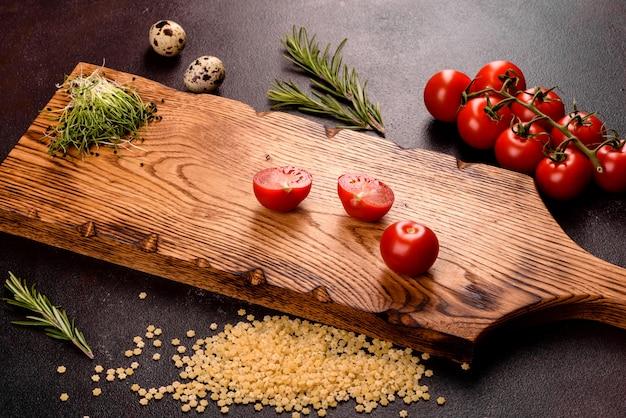 Składniki do pasty do gotowania. pomidory koktajlowe, przyprawy i zioła przygotowane na makaron