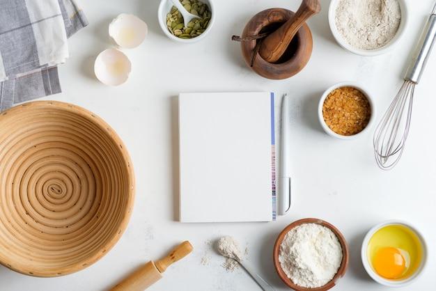 Składniki do pieczenia do gotowania tradycyjnego domowego chleba z papierem do przepisu na jasnoszarym marmurowym stole.