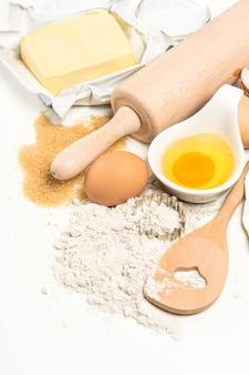 Składniki do pieczenia jajka, mąka, cukier, masło. przybory kuchenne. tło żywności