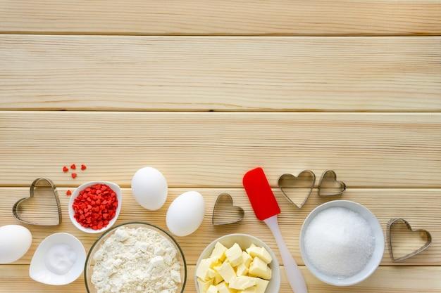 Składniki do pieczenia na ciasteczka, słodkie posypki i przybory kuchenne miejsce na tekst.