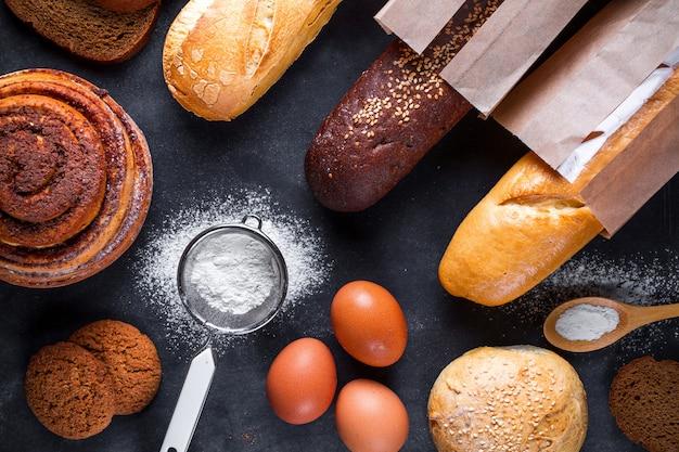 Składniki do pieczenia produktów piekarniczych z mąki i żyta. świeży chrupiący chleb, bagietka zapakowana w papierową torbę i bułeczki