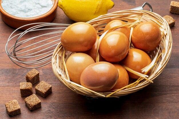 Składniki do pieczenia (świeże jajka, cukier, cytryna, mąka). zbliżenie oglądane z góry.