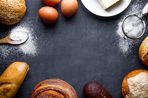 Składniki do pieczenia wyrobów piekarniczych. świeży domowy chrupiący chleb, bagietka, bułeczki na czarnym tle ramki tablicy