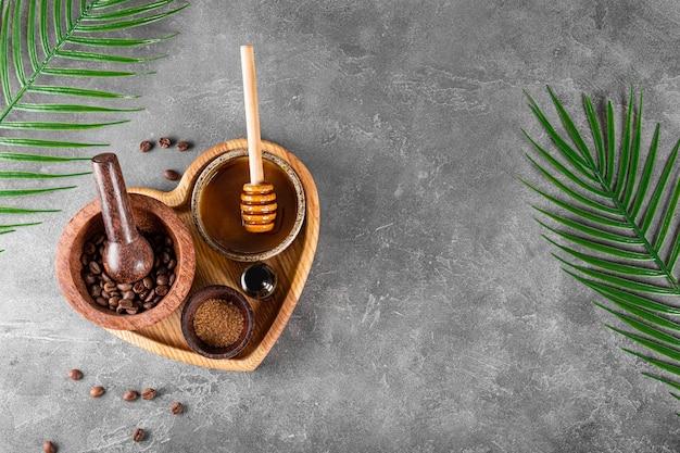 Składniki do przygotowania domowego peelingu kawowego do pielęgnacji skóry na talerzu w kształcie serca i szarym tle
