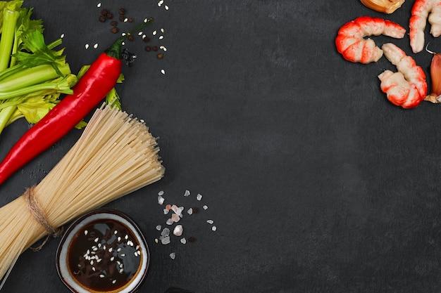 Składniki do przygotowania smażonego makaronu z krewetkami, owocami morza, sosem sojowym i przyprawami układane są na czarnym kamieniu