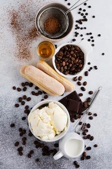Składniki do przygotowania włoskiego deseru tiramisu, savoiardi, mascarpone, kakao w proszku i czekolady na jasnym betonie