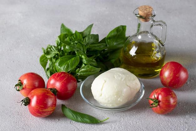 Składniki do przygotowania włoskiej sałatki caprese: pomidory, ser mozzarella, bazylia i oliwa z oliwek na jasnoszarym tle