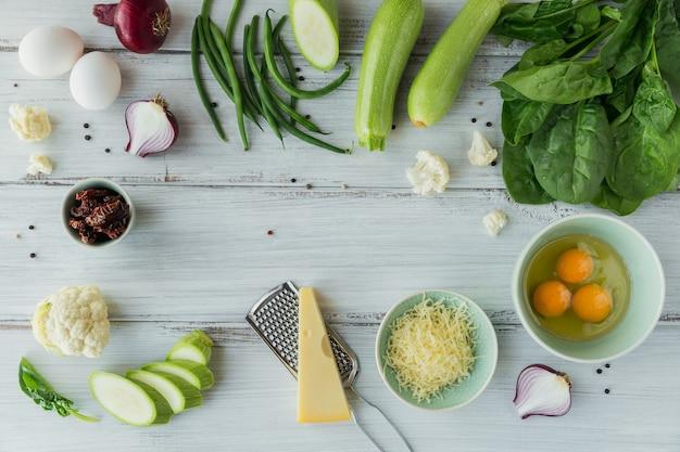 Składniki do przygotowania zdrowej wegańskiej żywności. kalafior, cukinia, czerwona cebula, fasolka szparagowa, jajka, ser i liście szpinaku do przygotowania warzywnej frittaty