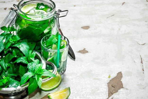 Składniki do robienia mojito - limonka, liście mięty, rum, nóż do cytrusów i stary stół. wolne miejsce na tekst