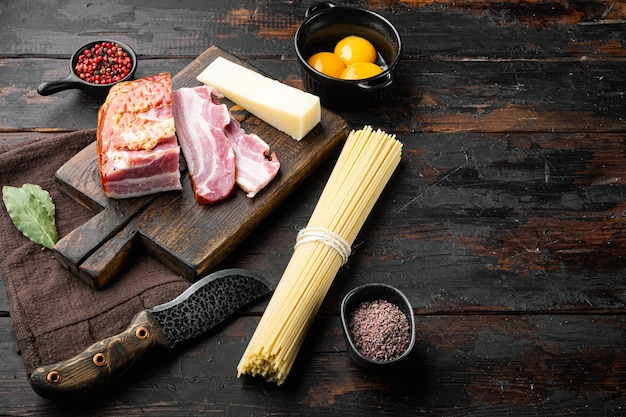 Składniki do robienia tradycyjnego włoskiego zestawu spaghetti carbonara, na starym ciemnym drewnianym stole, z miejscem na kopię