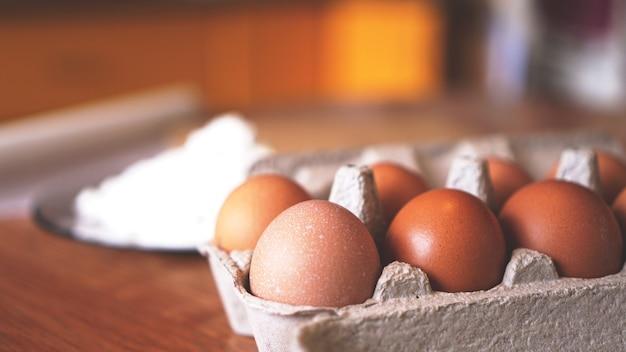 Składniki do wypieku domowego chleba. jajka, mąka. drewniane tła, widok z boku. miękka ostrość i światło