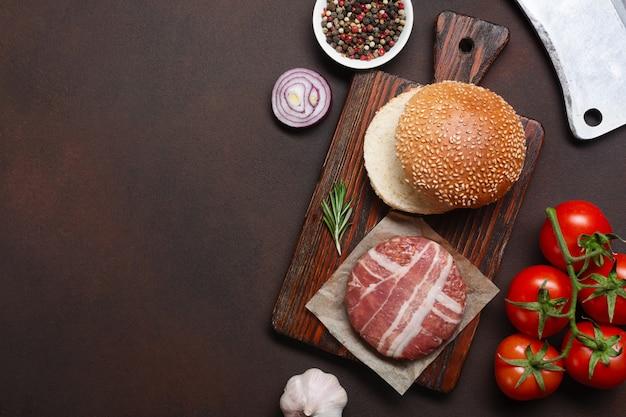 Składniki hamburgera: surowy kotlet, pomidory, sałata, bułka, ser, ogórki i cebula