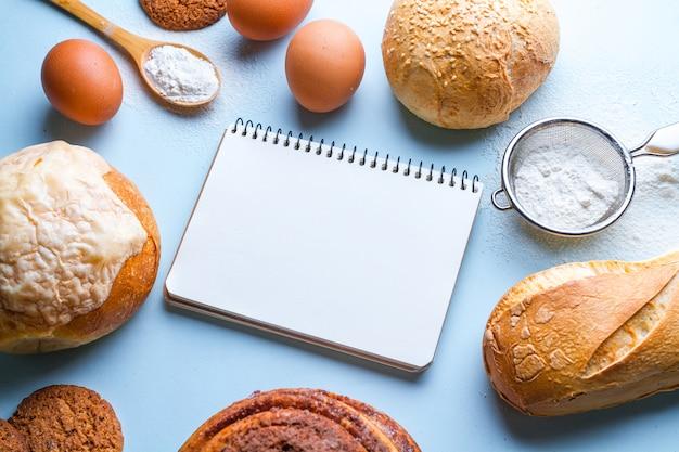 Składniki i książka kucharska do pieczenia produktów piekarniczych. świeży chrupiący chleb, bagietka i babeczki na błękitnym tle.
