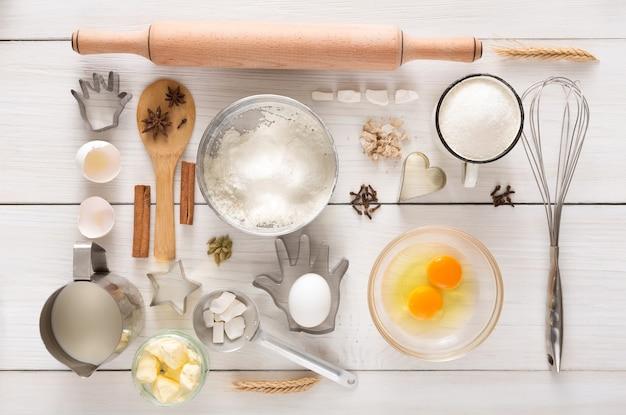 Składniki i naczynia do gotowania ciasta drożdżowego i ciasta na białym drewnie rustykalnym. widok z góry, płaski układ